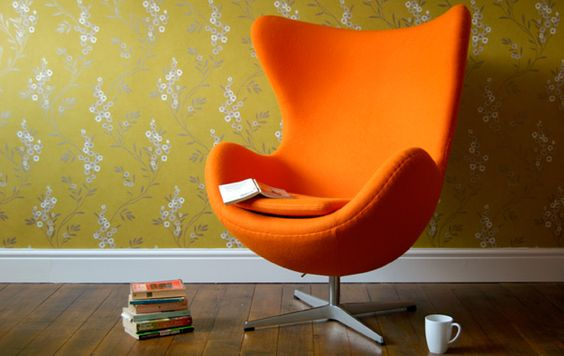 egg chair in bright orange vintage flower wallpaper in olive green color wood floors