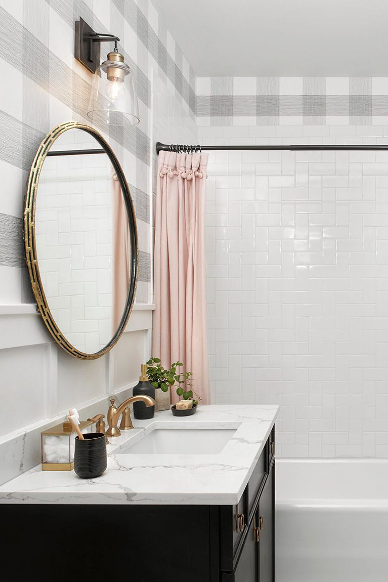 girly bathroom buffalo check wallpaper ceramic tile walls pastel tone shower curtains round shape mirror with brass frame brass hardware marble countertop black painted cabinets