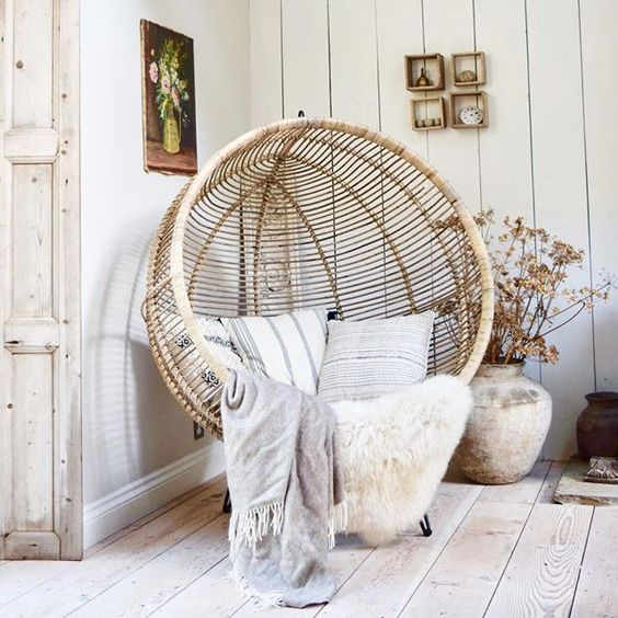 hanging rattan chair featuring sheepskin throw pillows and throw blanket antique pot reclaimed wood floors