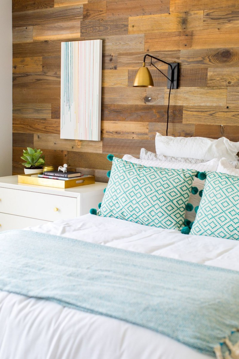 headboard wall accent made of wood white nightstand white bedding patterned pillows in turquoise wall mounted light fixture with gold tone lampshade