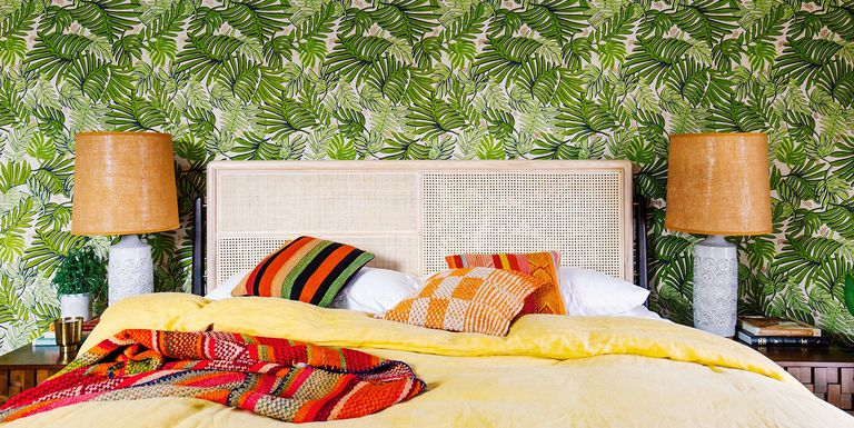 leave printed wallpaper in green a pair of table lamps with ceramic base and earthy brown lampshade