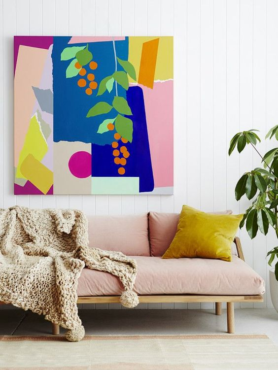 midcentury modern sofa with baby pink cushion and wood frame pastel pink throw blanket bold painting without frame