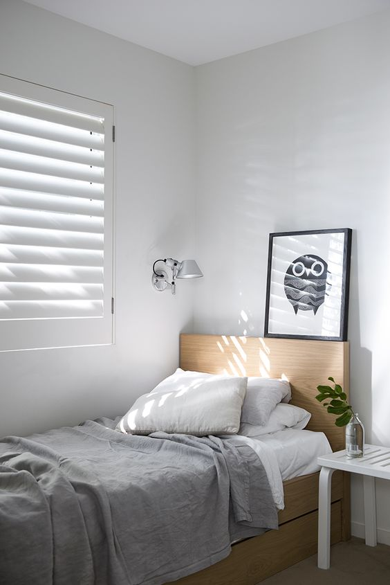minimalistic teen bedroom light wood bed frame with headboard window with white shutter light gray blanket white side table