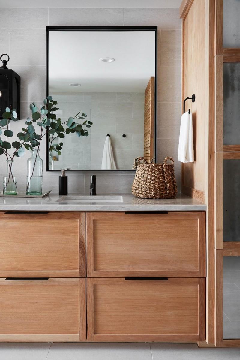 modern spa like bathroom marble countertop wood cabinetry black framed mirror decorative basket black hardware