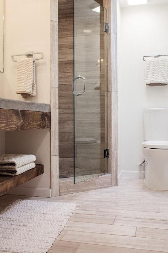 modern walk in shower with fully wood finish inside and glass door light wood floors
