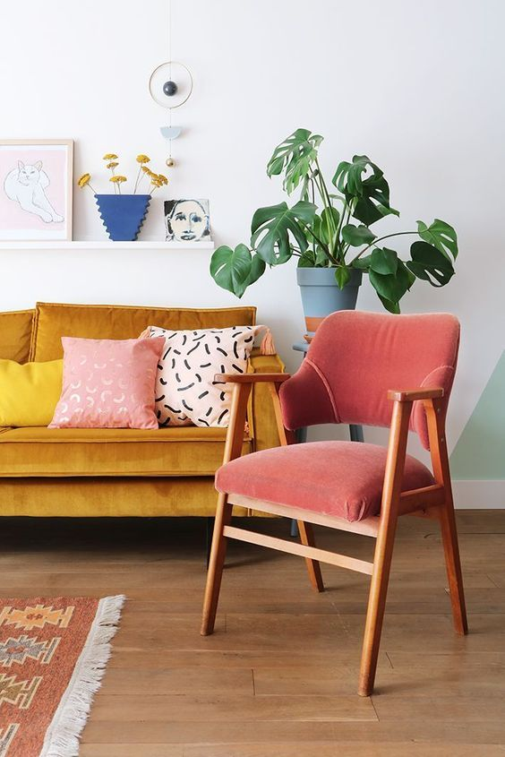 mustard sofa with colorful throw pillows deep pink chair with wood frame light wood floors houseplant with blue plastic planter