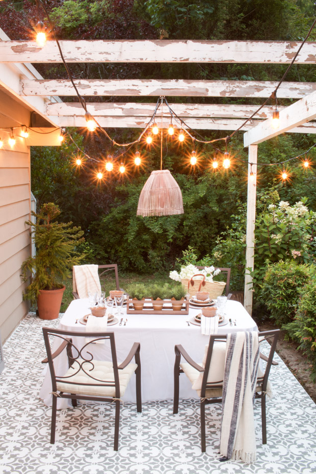 neutral furniture pieces bold patterned tile floors shabby wood beams with string of outdoor bulbs pendant with bamboo lampshade