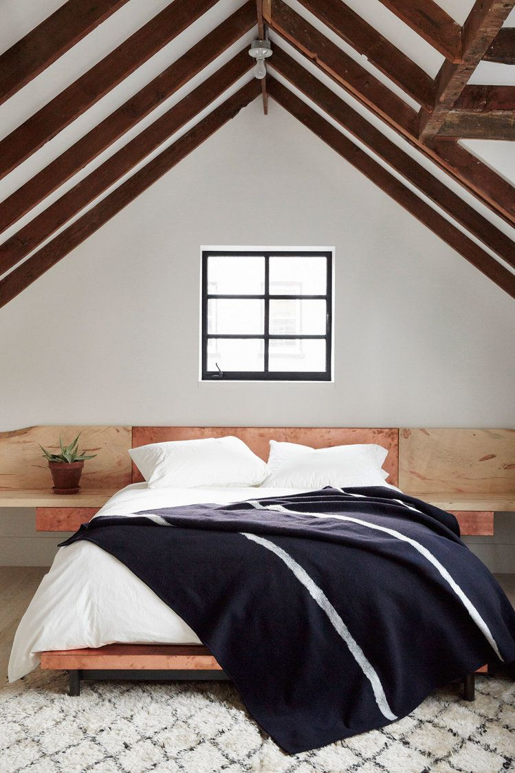 neutral teen bedroom extended light wood white crisp wall painting slanted roofs exposed wood beams centered window fluffy carpet