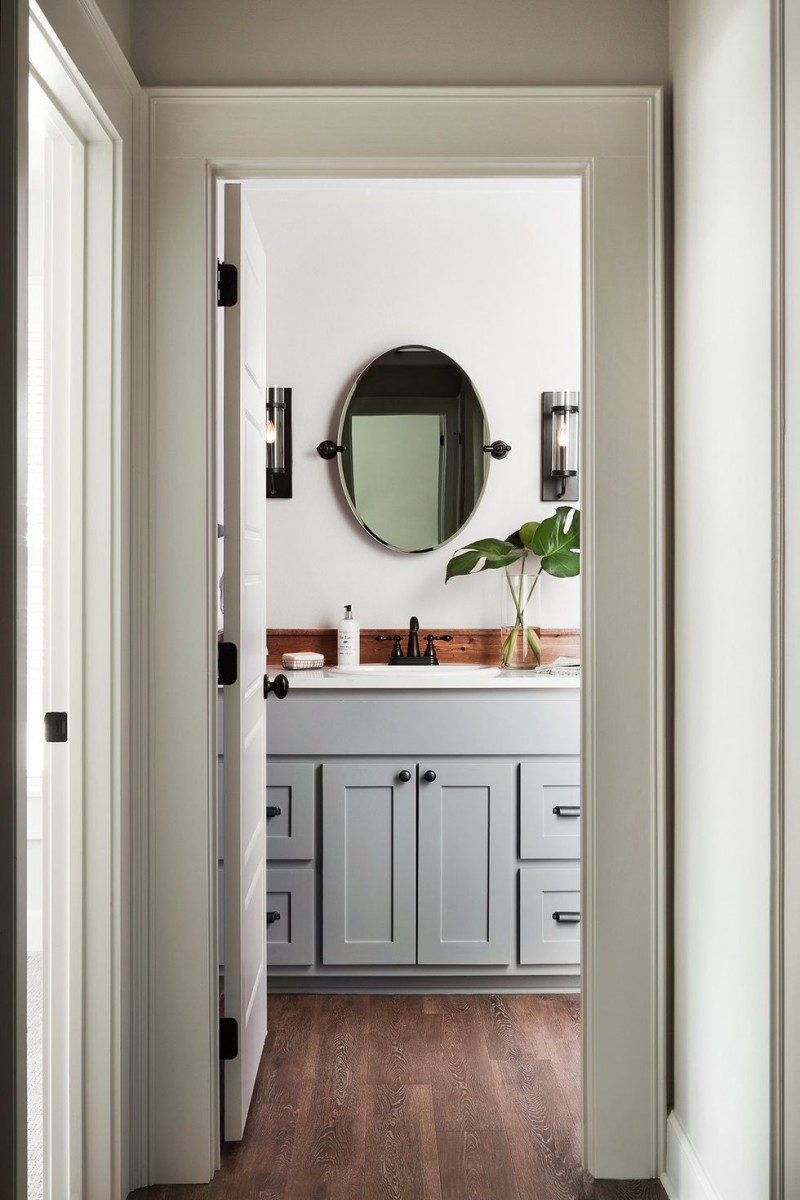 neutral tone vanity bathroom gray cabinets wood backsplash oval shape wall mirror greenery with glass pot