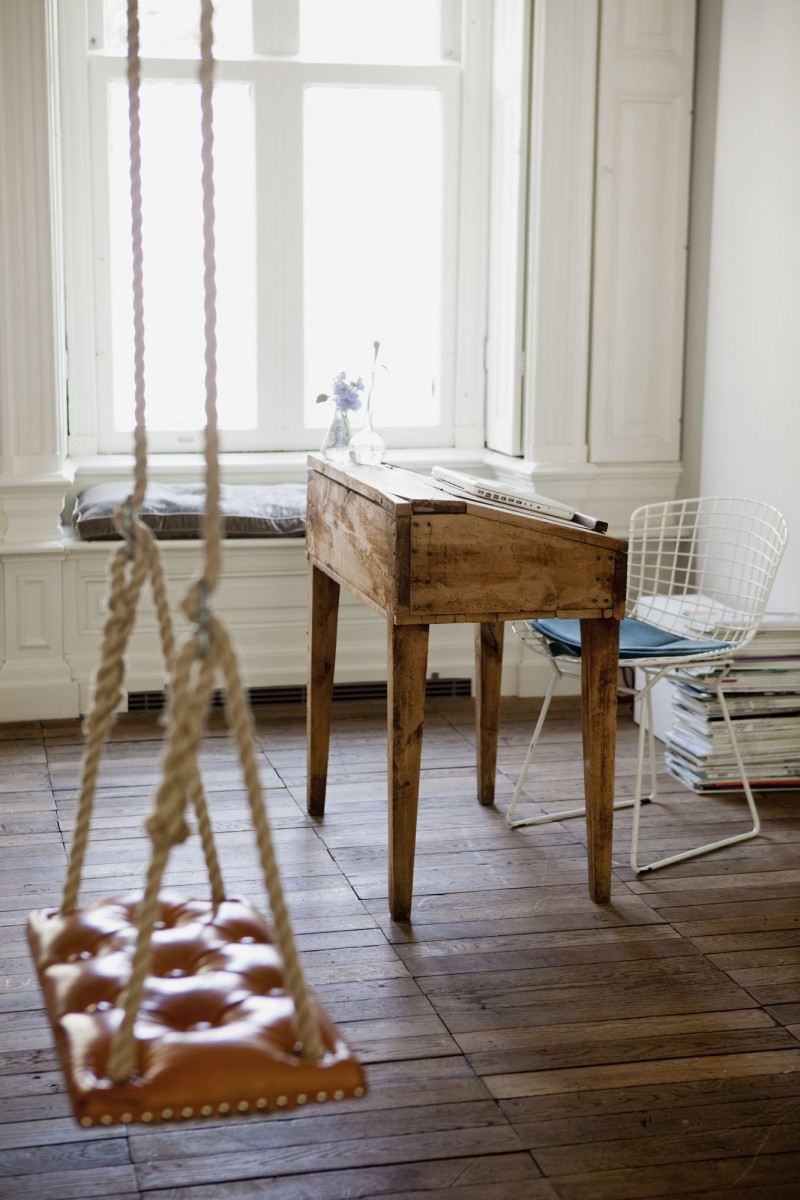 raw wood working desk in midcentury modern style wire metal chair in white wood plank floors