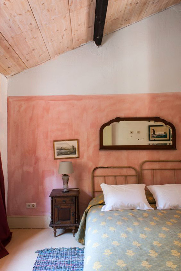 saturated pink wall featuring with white light wood ceilings with exposed wood beams in black classic metal bed frame with headboard old look nightstand made of wood