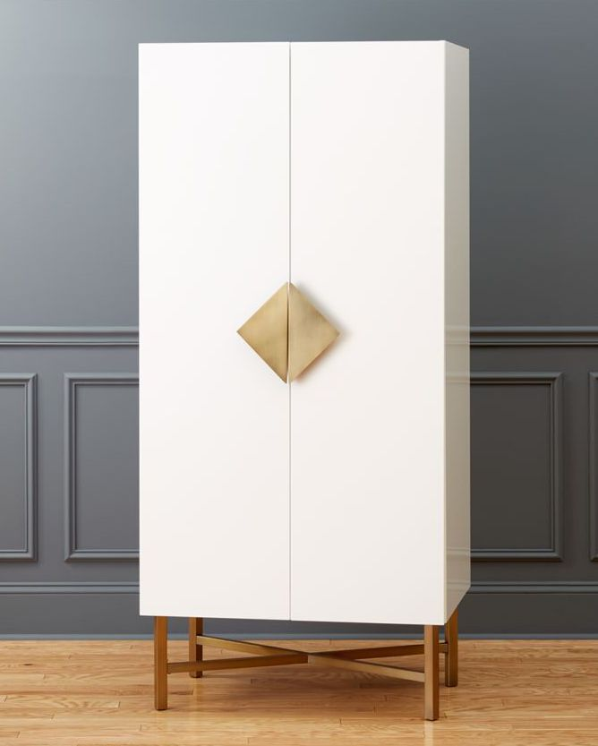 simple armoire wardrobe in white supported with gold tone geometric handle and wood legs