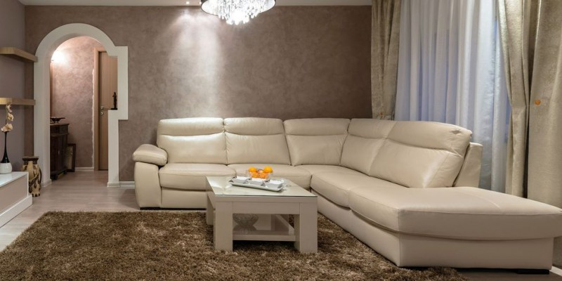 sponge like wall painting in nude broken white sofa with armrest and additional chaise glass top coffee table in white comfy area rug
