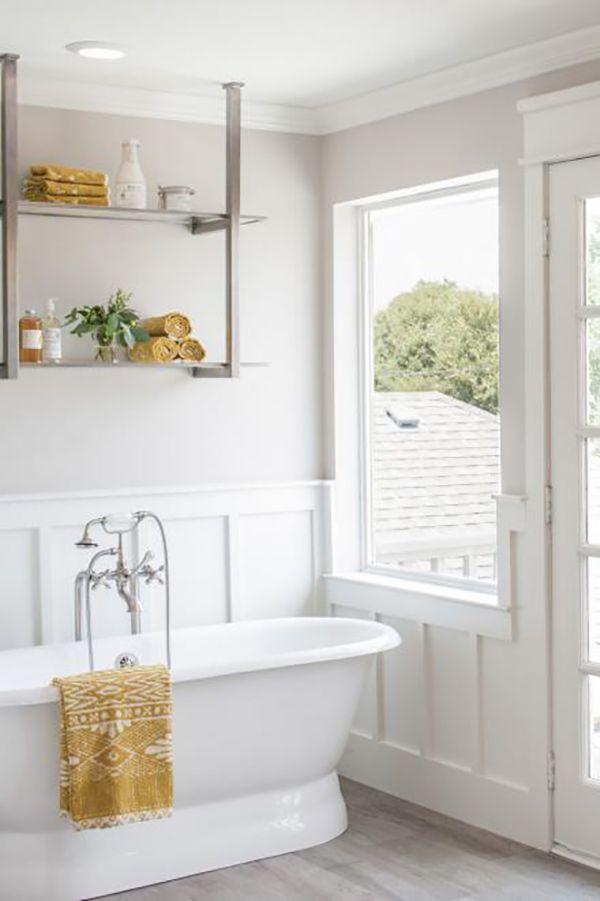 sunny spa like bathroom white bathtub hanging rack white tone wood floors glass window private balcony