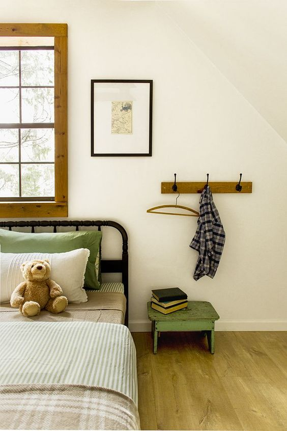 traditional bed frame with headboard wood frame window black frame painting light wood floors low level side table in shabby green color