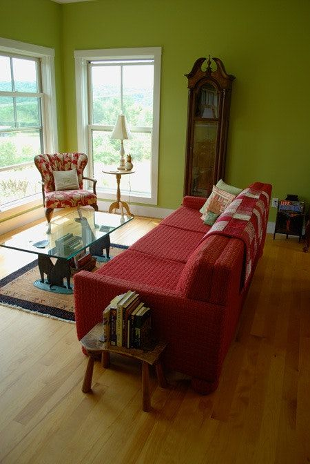 warm green olive walls glass windows with white trims bold red sofa with throw blanket glass top coffee table