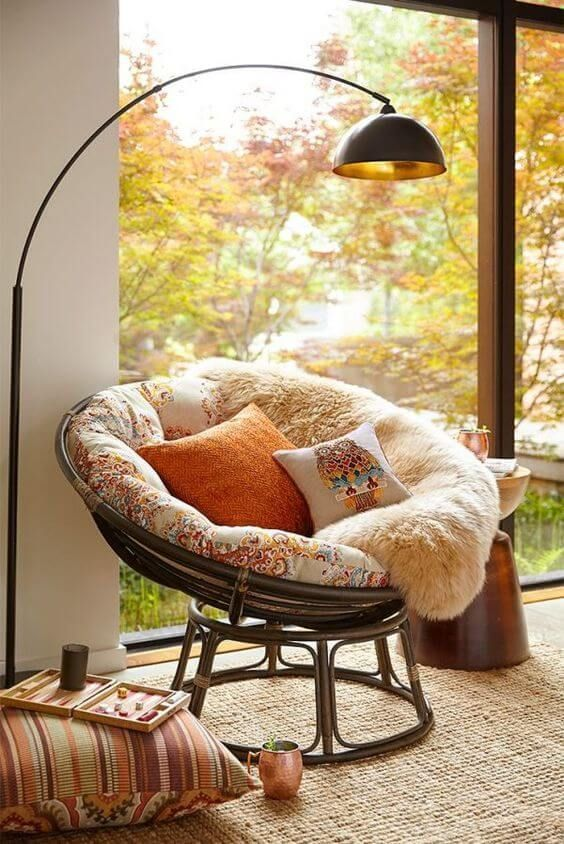 Boho style reading nook egg chair in black with throw fur blanket and foamy cushion floor pillow in Boho modern floor lamp in black