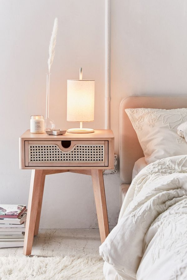 Marte nightstand by Urban Outfitters with woven rattan drawer accent in midcentury modern style dimly lighted table lamp