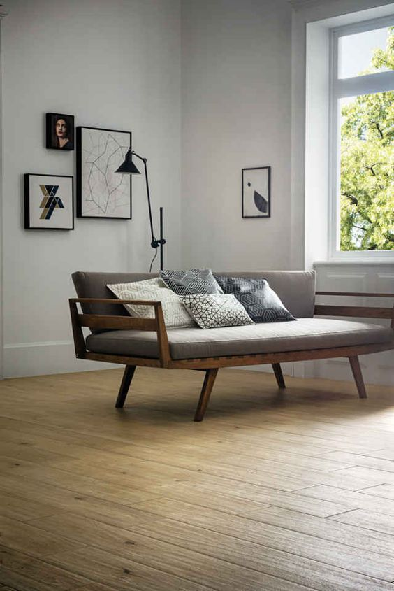 airy living room design white walls with some framed pictures midcentury modern sofa with dark wood frame and gray cushion addition wood floors glass windows