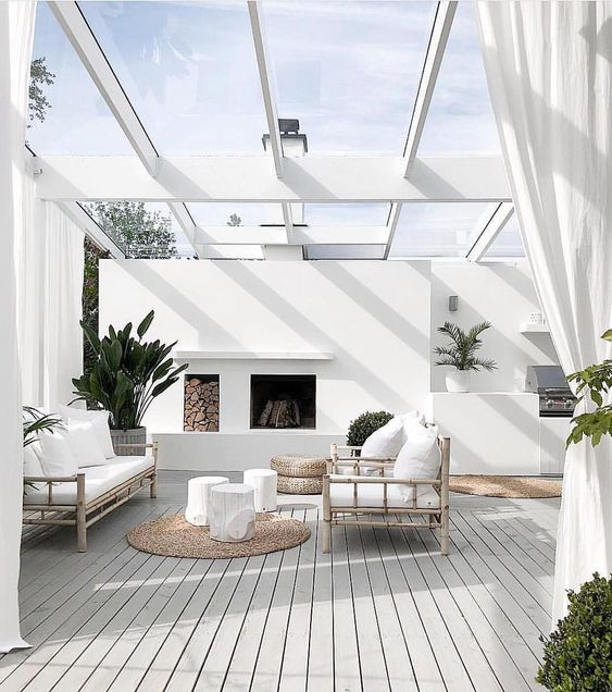 beach style backyard with glass shade white curtains bamboo frame chairs white stool tables woven rug in round shape