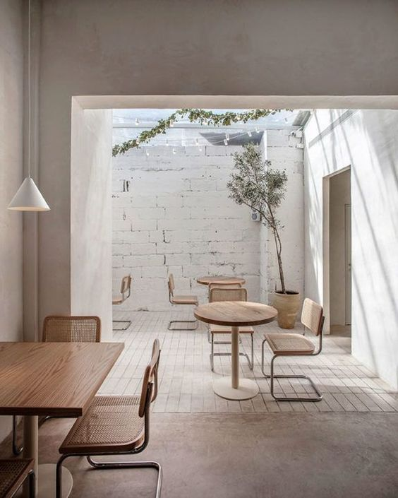 bright and airy commercial space white brick walls white finish concrete walls white tile floors concrete floors light wood furniture sets