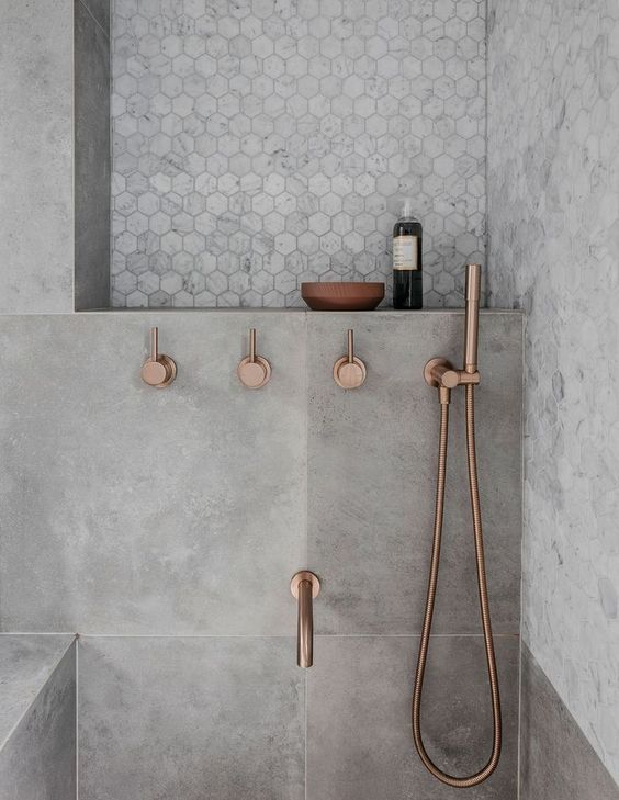 concrete finish walls with hexagon patterned tiles metallic shower fixtures in copper tone