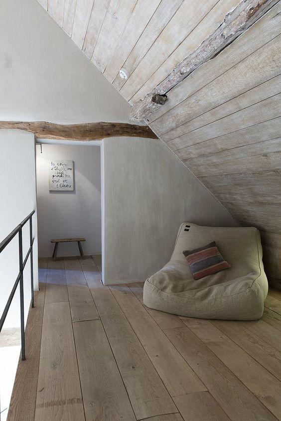 corner seating area slanted roofs wood plank floors floor cushion in gray concrete walls