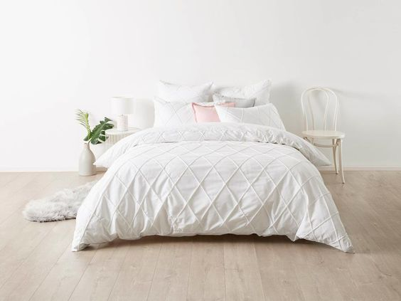 crisp white bedroom wall idea crisp white bed treat and duvet cover light wood floors white chair houseplant with white pot