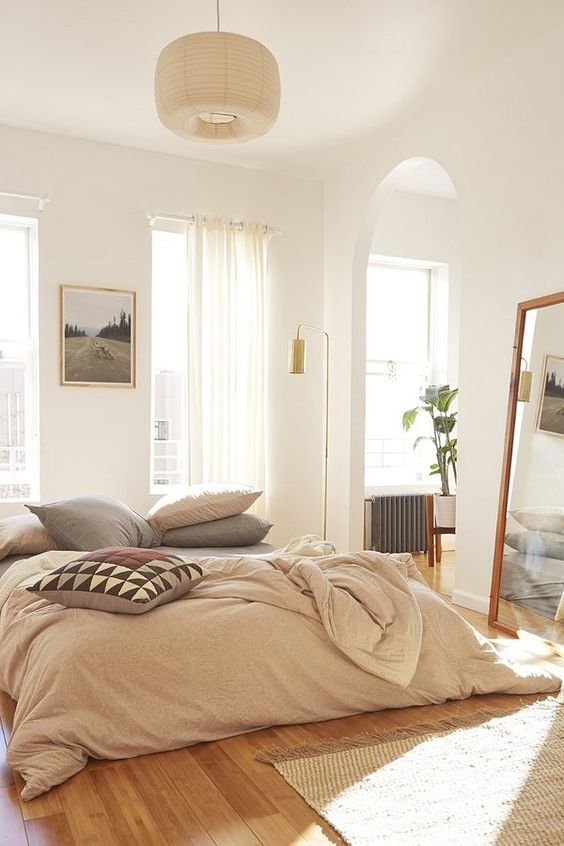 light and airy bedroom design duvet cover in pastel wood floors leaning mirror with wood frame woven rug semi transparent curtains in white glass windows