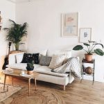 Light Neutral Living Room Midcentury Modern Sofa In White Midcentury Modern Coffee Table With Pointed Legs Round Shape Jute Area Rug Potted Palm And Greenery
