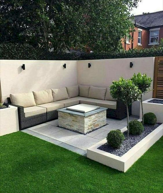 modern minimalist sitting area L shaped leather sofa in broken white built in table green grass bed ornate plants on concrete planters