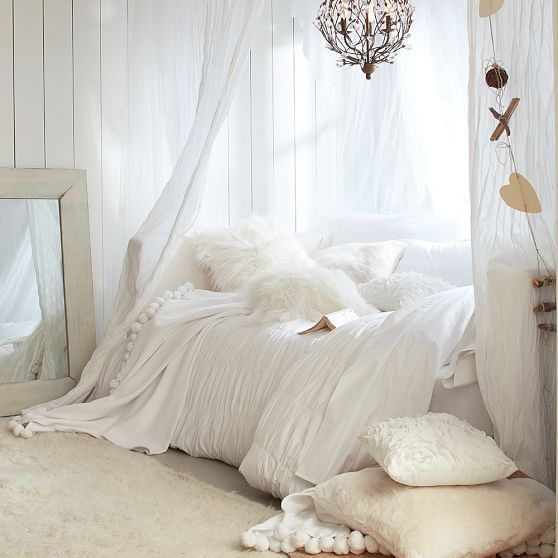 off white wood plank walls broken white frame leaning mirror white bed treat with white duvet cover bed canopy in white