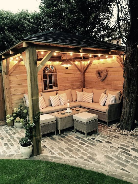 outdoor seating nook with string lamps L shaped sofa some throw pillows and some coffee tables