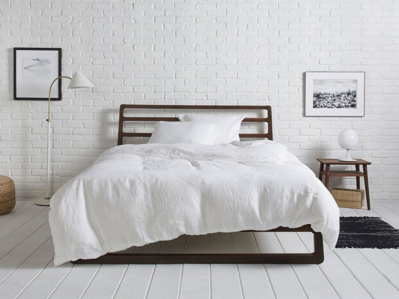 pure white duvet cover by Parachute white painted brick walls white floor lamp dark bed frame with headboard white wood plank floors
