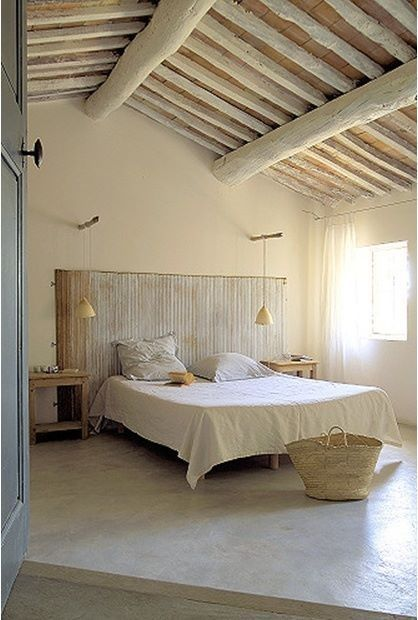 rustic farmhouse bedroom in pale tone pale wood beams white concrete floors pale tone walls white bed linen shabby headboard
