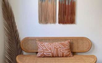 sitting corner wicker loveseat with a throw pillow feather like ornament Boho wall decor