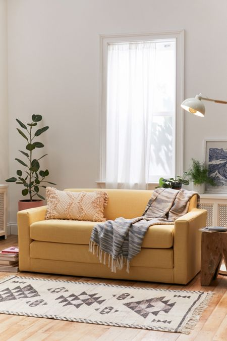 sleeper sofa in sunshine yellow by Urban Outfitters throw pillow throw blanket scandinavian runner