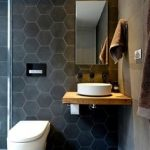 Small Bathroom For Apartment Black Hexagon Tile Walls Gray Concrete Floors Wall Mounted Toilet In White Frameless Mirror Wood Countertop And White Ceramic Sink