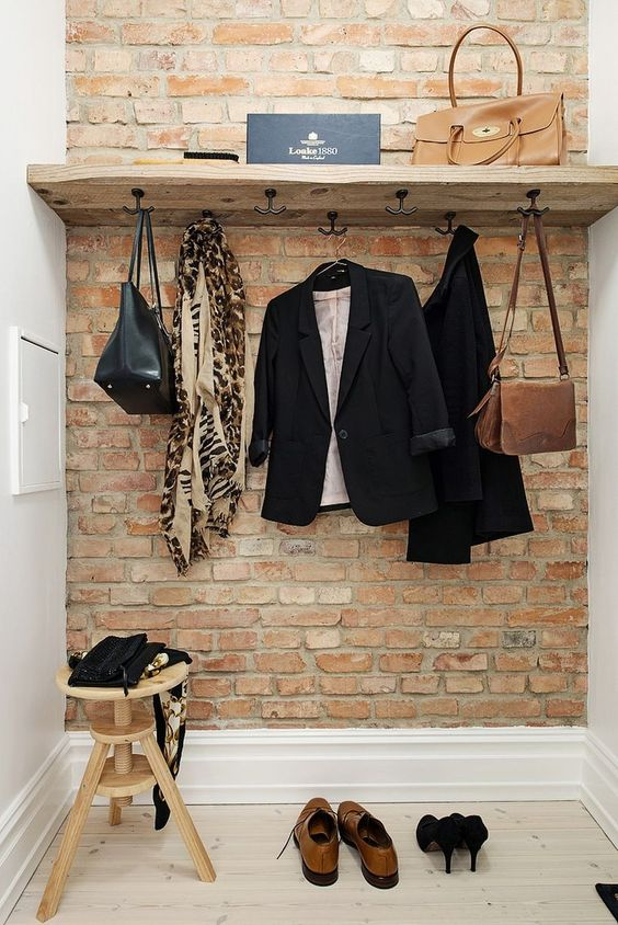 small walk in closet idea red brick accent wall wood shelf with hooks under white walls and floors wood stool