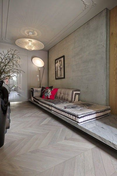 softer concrete finish walls and ceilings herringbone patterned wood floors floor cushions with motifs