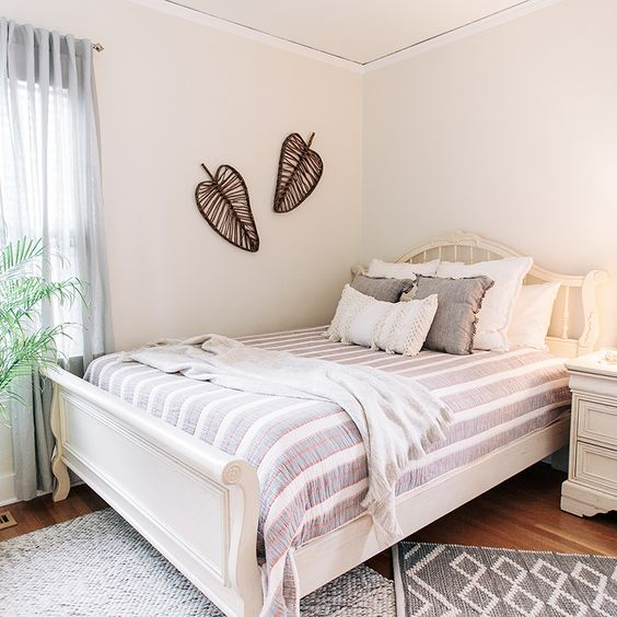 warm white bedroom wall idea with leave shape wall decors white bed frame with headboard striped bed linen white throw blanket white bedside table wood floors