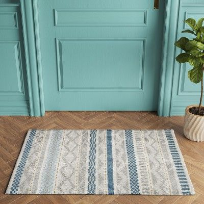 woven accent rug with geometric patterns in blue and gray
