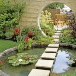 Asian Inspired Backyard Idea With Round Shaped Koi Pool With Concrete Walkway Lots Of Green Plants