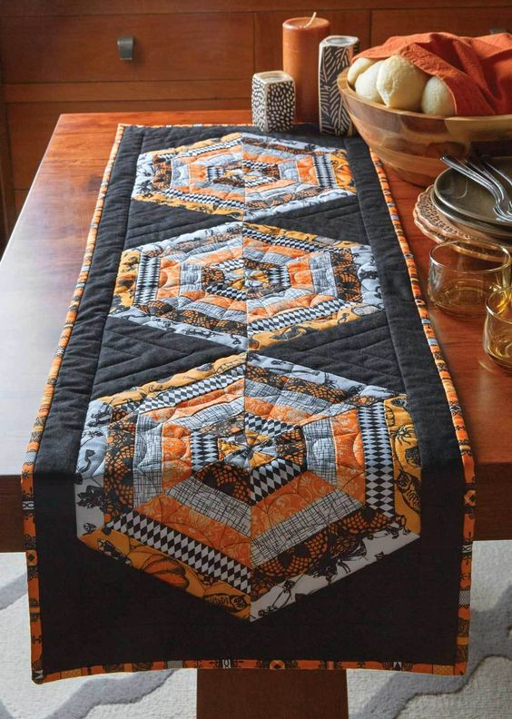 Halloween quilt table runner with multicolored geometric patterns in the middle