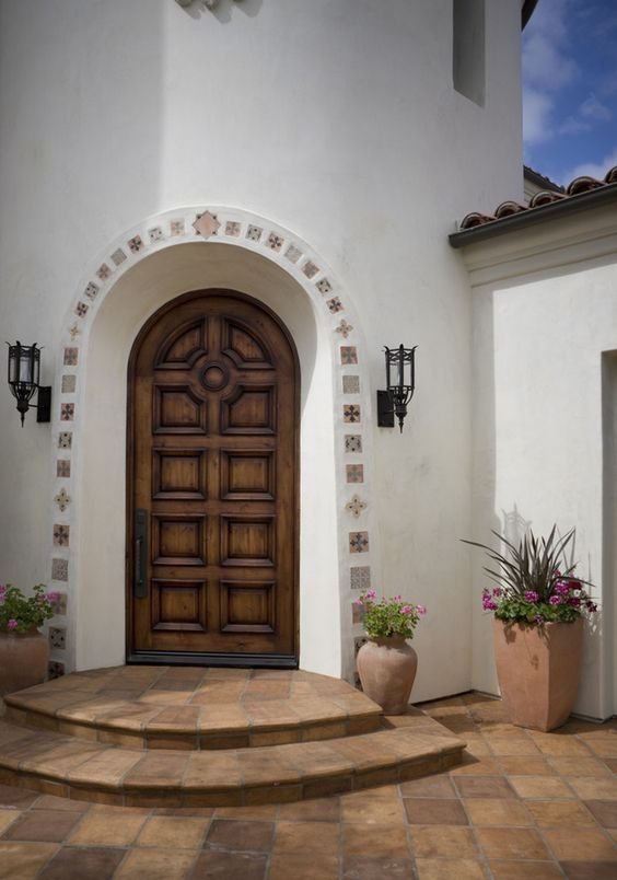 Mexican exterior design curved top wooden front door curved top front gate terra cotta tile floors white finish stucco wall