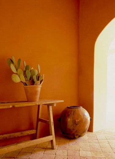 Mexican style entryway stucco walls in deep orange brick floors wood bench as table ornate clay made pot