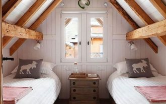a couple of single bed frames with white linen center dresser wood plank walls and ceilings in white exposed wood beams on ceilings