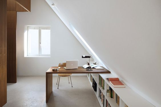attic workspace wood working desk simple and modern working chair under bookshelves