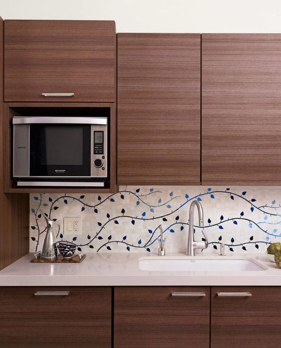 backsplash with leaves shaped accents white kitchen countertop dark wood kitchen cabinetry