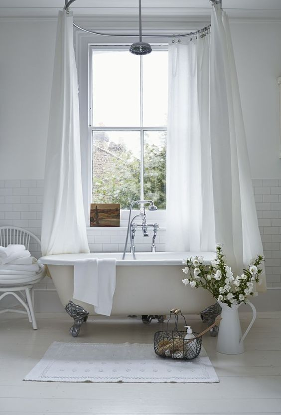 bright and airy bathroom design claw feet bathtub in white white shower curtains shower mat in white white chair